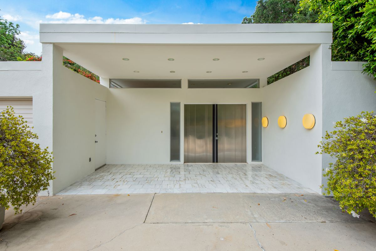 A box-like entryway with white walls and silver double doors