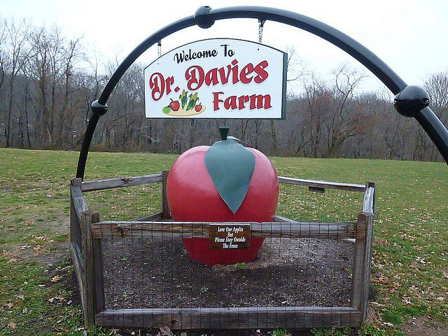 There is a sign that reads: Welcome to Dr. Davies Farm. Under the sign is a cart with a giant sculpture of a red apple. In the distance are trees.