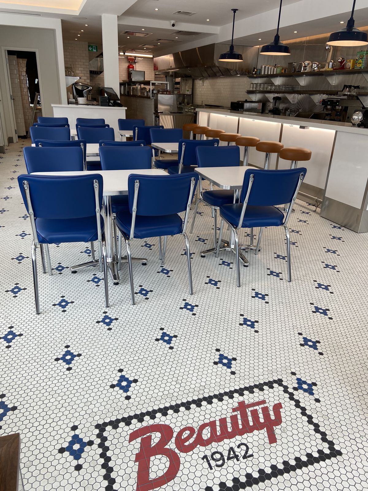 inside diner with mosaic flooring and blue seating
