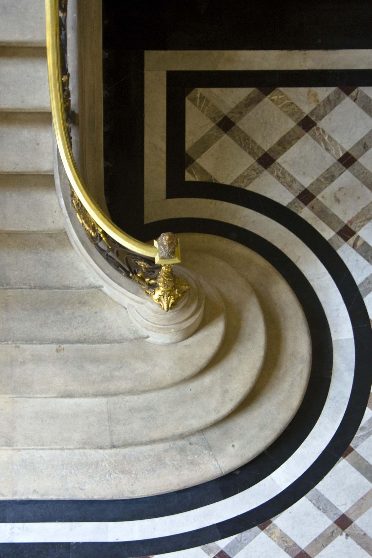 An aerial view of a Parisian staircase. The steps are marble and there is a patterned floor at the base of the staircase.