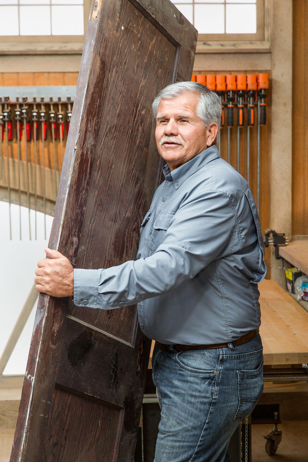 Pessoa carregando uma velha porta de madeira para uma mesa de oficina para que possam convertê-la em uma caixa de sombra.
