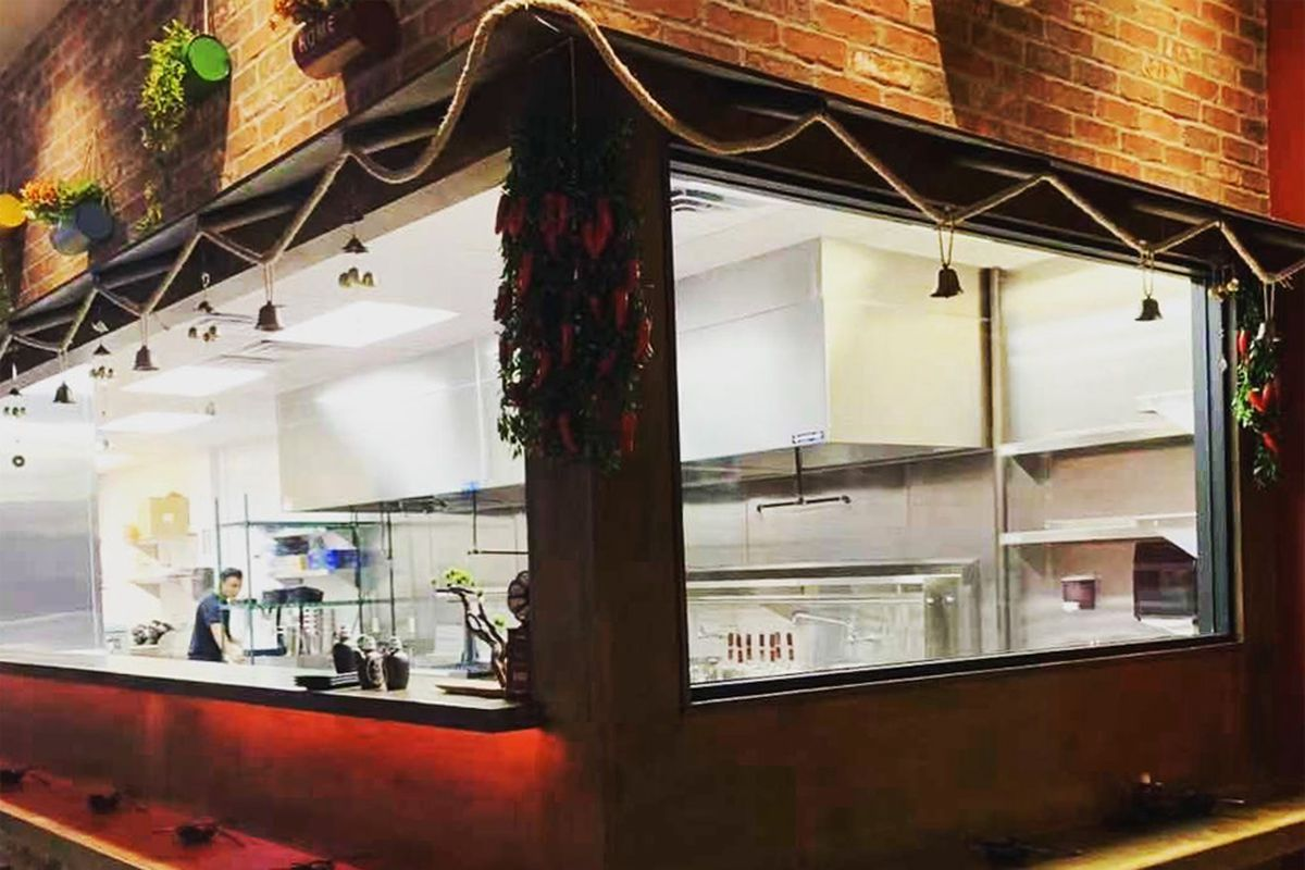The open window kitchen at The Noodle Man restaurant, where cooks hand pull noodles