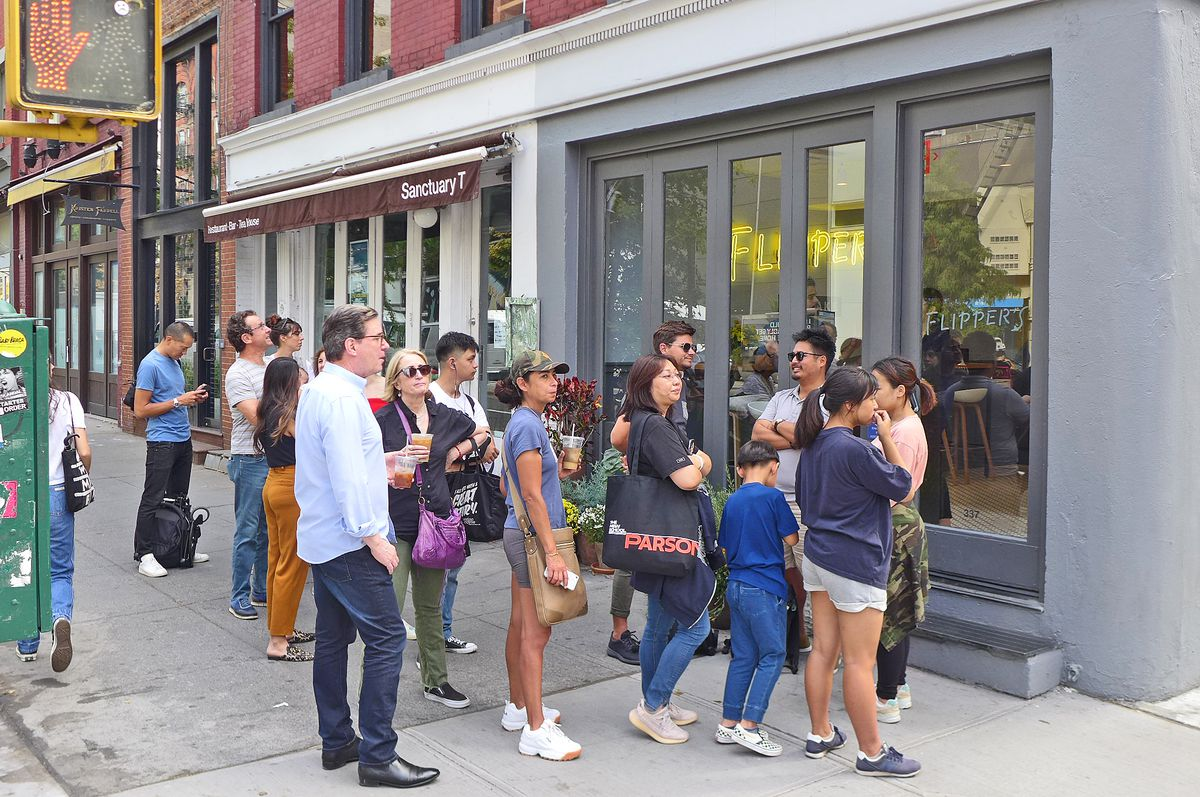 A straggly line of people wait outside the corner storefront, with a yellow neon Flipper's sign visible through the window...