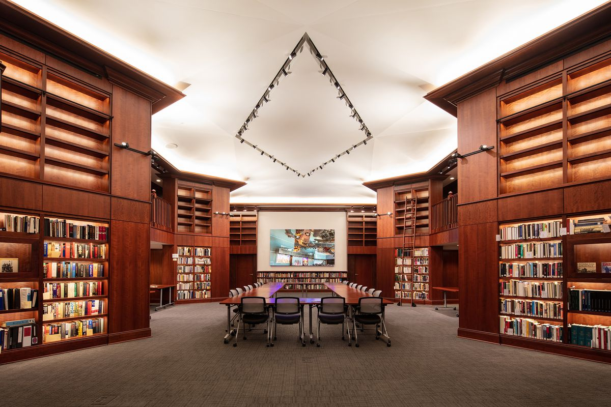 A rectangular conference table surrounded by chairs sits in the middle of a room with tall cherry-red bookshelves on either side and a gray carpet. Tracking for lights on the ceiling form a diamond.