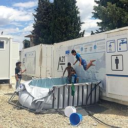 Young refugees at the Diavota refugee camp in northern Greece take turns jumping into an improvised swimming pool rigged out of tarps and rails in July 2016.
