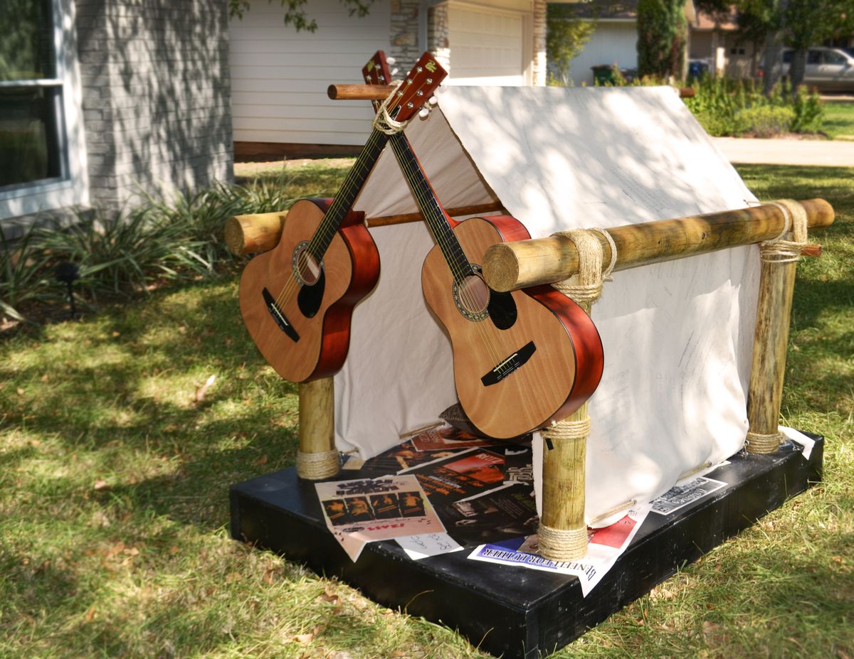 Outdoor shot of a tent-like dog house with acoustic guitars's necks crossed across the entrance.