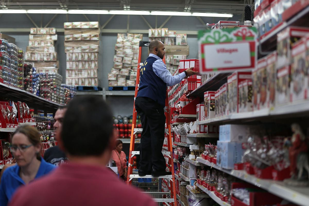 A man stands on a red ladder, arranging products on a shelf.