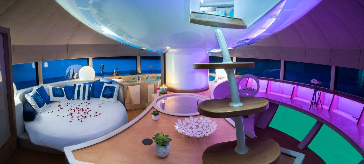 The interior of the floating pod lit up with glowing purple lights on the right. A circular bed with blue pillows sits on the left. The whole room is surrounded by rectangular windows looking out to sea and there is a narrow staircase leading to an upper
