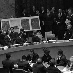 FILE - In this Oct. 25, 1962 file photo, U.S. Ambassador Adlai Stevenson, far right, describes aerial photographs of launching sites for intermediate range missiles in Cuba during an emergency session of the United Nations Security Council at U.N. Headquarters at the height of the Cuban Missile Crisis. Israeli Prime Minister Benjamin Netanyahu's use of a cartoon-like drawing of a bomb to convey a message over Iran's disputed nuclear program this week, follows in a long and storied tradition of leaders and diplomats using props to make their points at the United Nations.