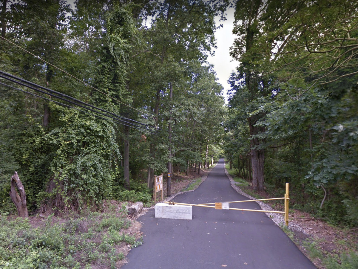 A metal barrier blocks cars from entering a paved road. Behind it, thick greenery and trees.