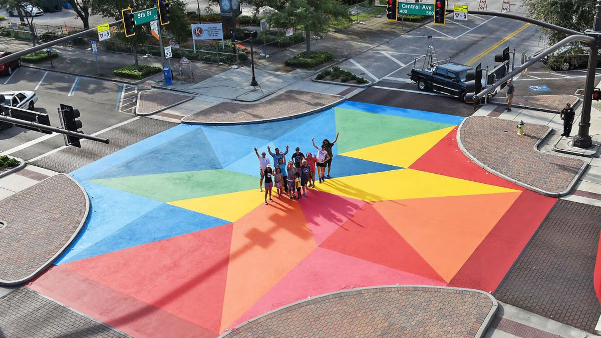 An aerial view of a street intersection painted in bright colors like blue, yellow, and red.