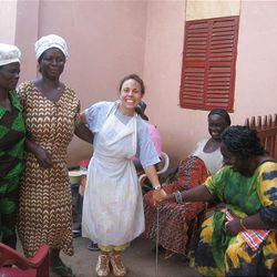 A volunteer with Empowering Nations helps women cook lunches for a school program.