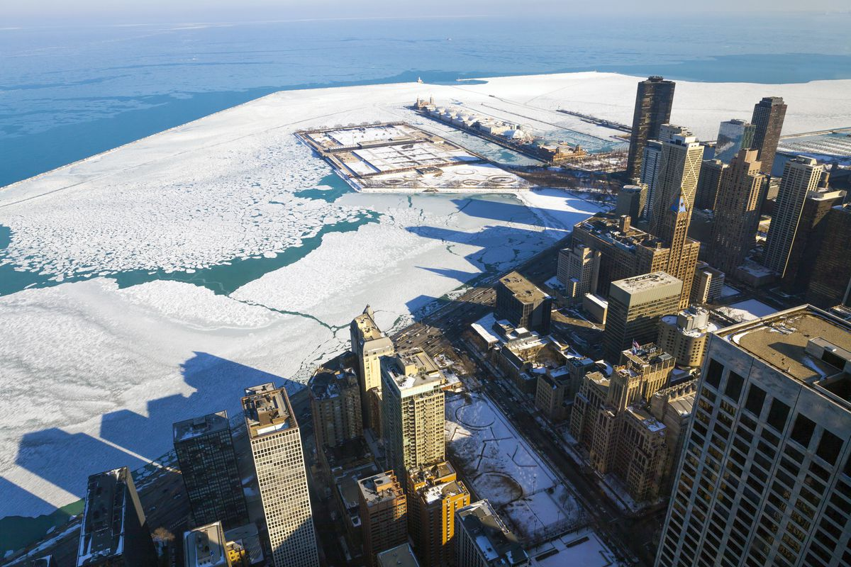 An aerial view of Chicago in the snow. The water surrounding Chicago is ice.