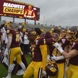 Branden Barker (49), Mark Pattrio (13) and Devonni Reed (5) celebrate as the CMU football team sprints to the CMU Marching Band.