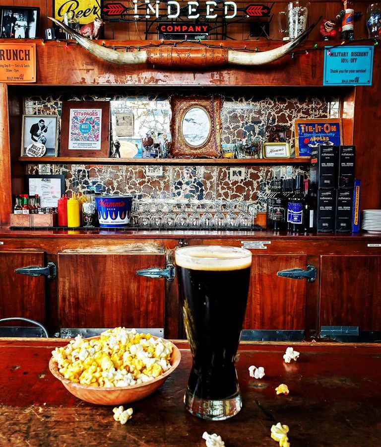 The back bar featuring bull's horns, bags of chips, and on the bar is a dark beer with a bowl of popcorn