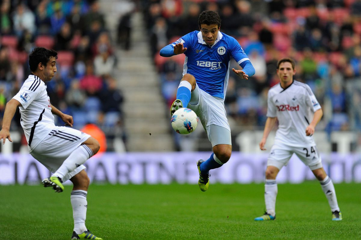 Swansea defender Neil Taylor (L) looks on as Wigan forward Franco Di Santo controls the ball during the Barclays Premier League match between Wigan Athletic and Swansea City at DW Stadium.