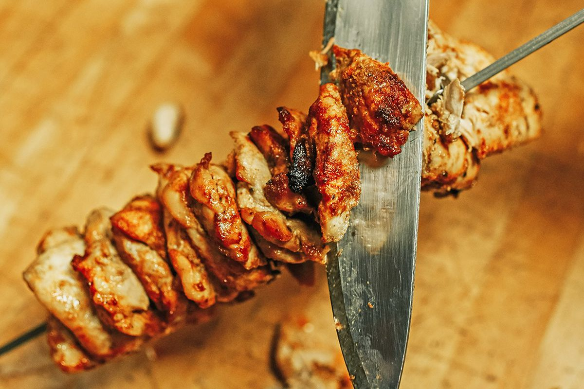 A sharp knife slices pieces of spit-fire roasted chicken from a metal skewer