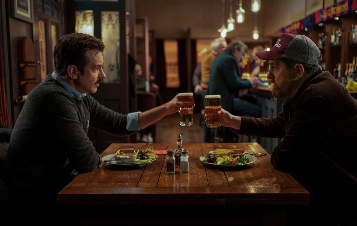 Jason Sudeikis clinks glasses in a pub with a friend in Ted Lasso