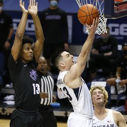 Brigham Young Cougars guard Alex Barcello (13) scores past Portland Pilots forward Eddie Davis (13) at the Marriott Center in Provo on Thursday, Jan. 21, 2021.