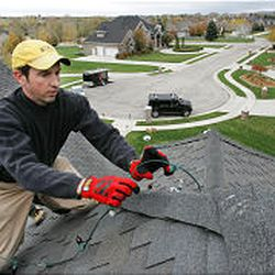 Vance Brand, co-owner of Christmas Light Professionals of Salt Lake City, installs lights on a Draper rooftop. Some homes have 50-foot drops to the ground.=