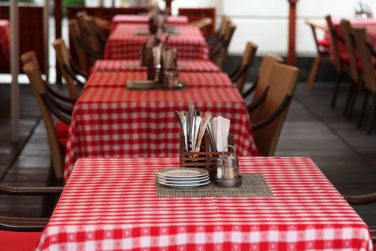 Empty restaurant tables set with red checkered tablecloths, silverware, and plates.