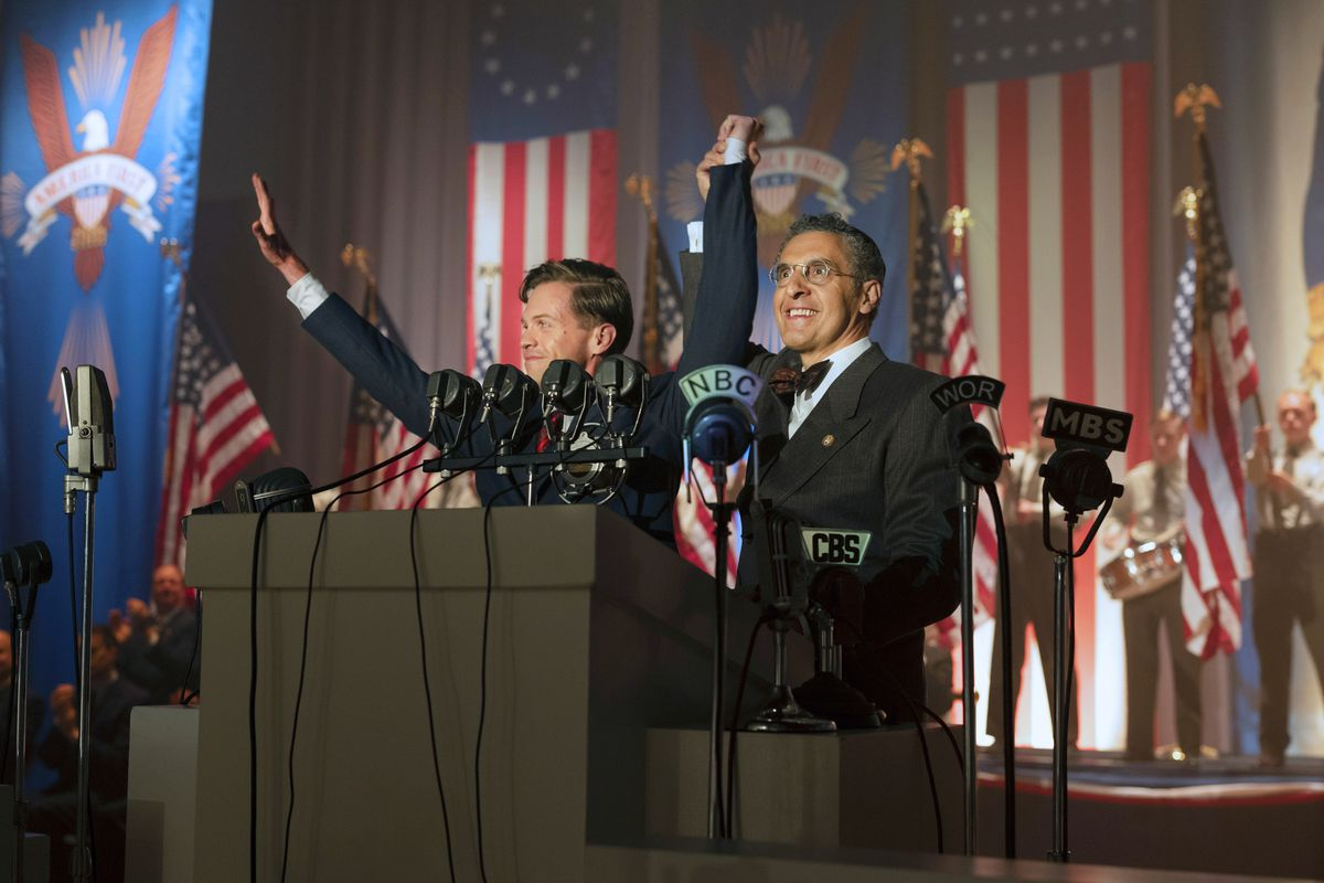 """In 1940, in the alternative-universe setting of The Plot Against America, a rabbi played by John Turturro stands with a manic grin in front of a wall of American flags and """"America First"""" banners, holding up the hand of a man who appears to be giving the Nazi salute."""