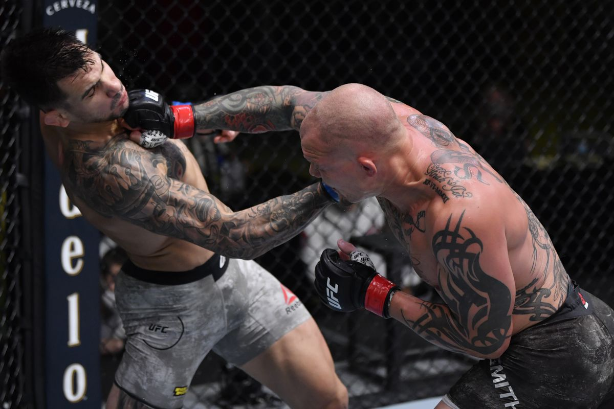 In this handout image provided by UFC, Aleksandar Rakic of Austria and Anthony Smith trade punches in their light heavyweight fight during the UFC Fight Night event at UFC APEX on August 29, 2020 in Las Vegas, Nevada.