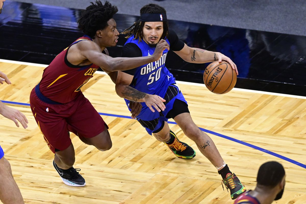Cole Anthony of the Orlando Magic dribbles the ball as Collin Sexton of the Cleveland Cavaliers defends during the first quarter at Amway Center on January 06, 2021 in Orlando, Florida.