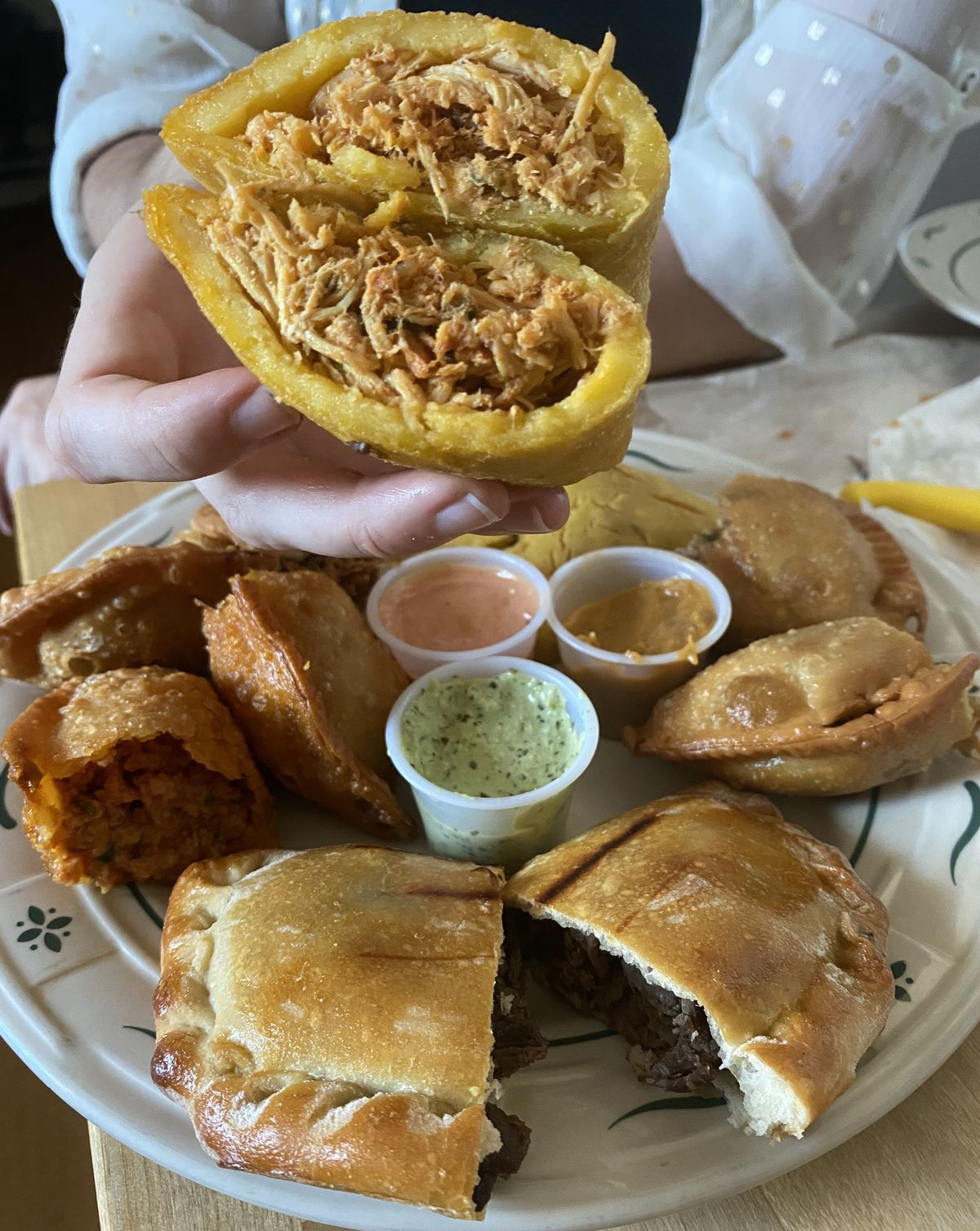 Six empanadas cut in half and displayed on a white plate with green designs on the edge. A person is holding one empanada up to the camera
