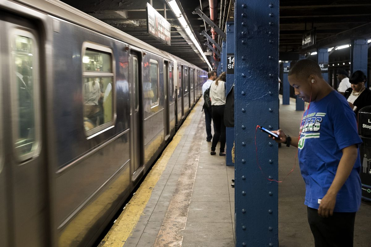 A man looks at his phone while standing on a subway platform.