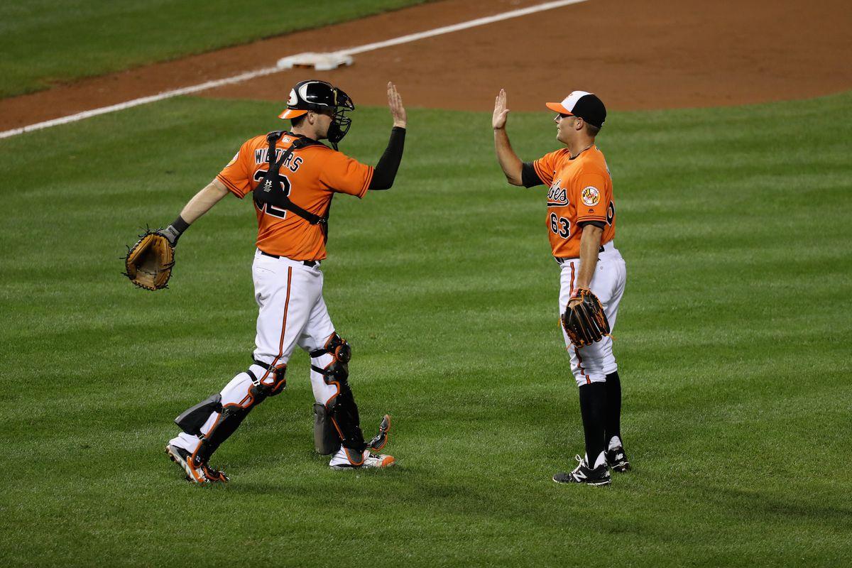 Matt Wieters and Tyler Wilson high five after an Orioles victory.