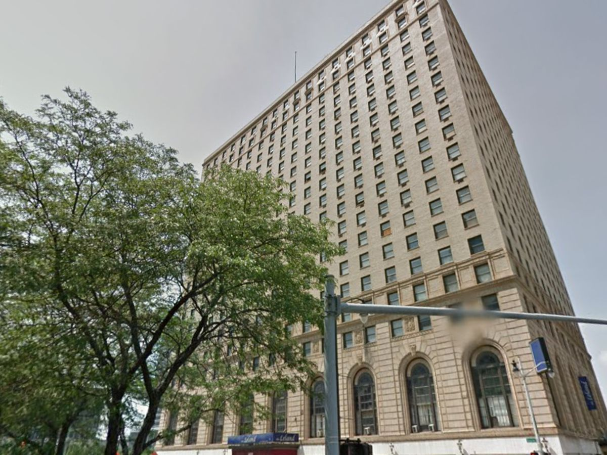 The exterior of the Leland Hotel in Detroit. The facade is tan with arched windows on the ground level. There are trees in front of the building.