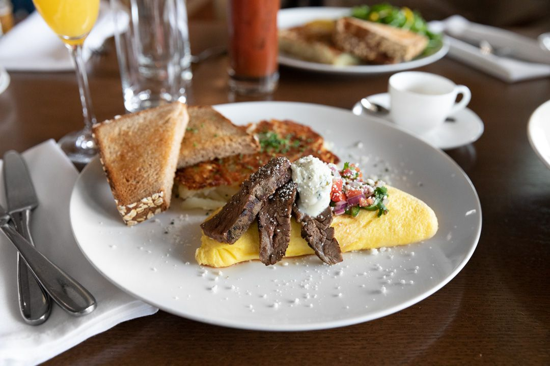 A breakfast plate with toast, hasbrowns, omlette topped with steak
