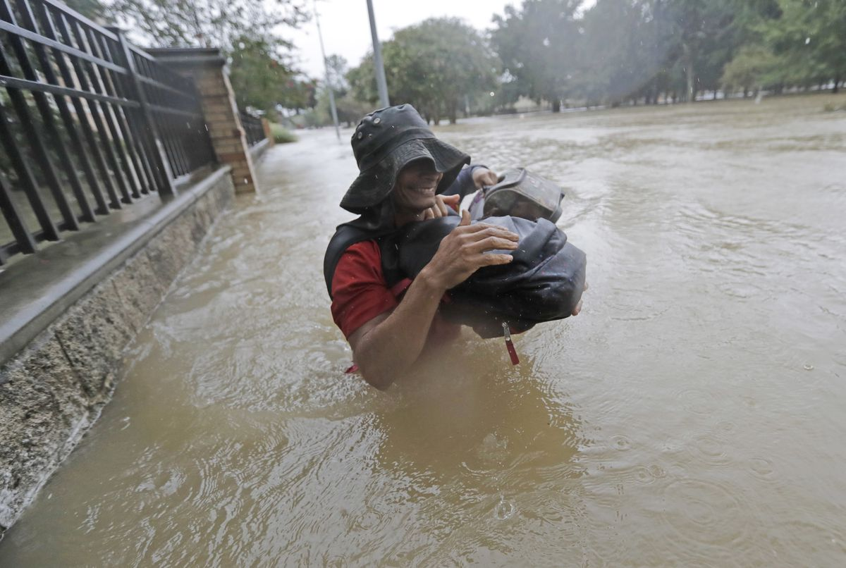 Residents wade through floodwaters from Tropical Storm Harvey Sunday in Houston. | David J. Phillip/Associated Press
