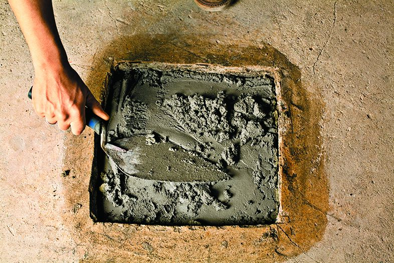 <p>3. Mix the concrete with water and scoop some into the hole</p>