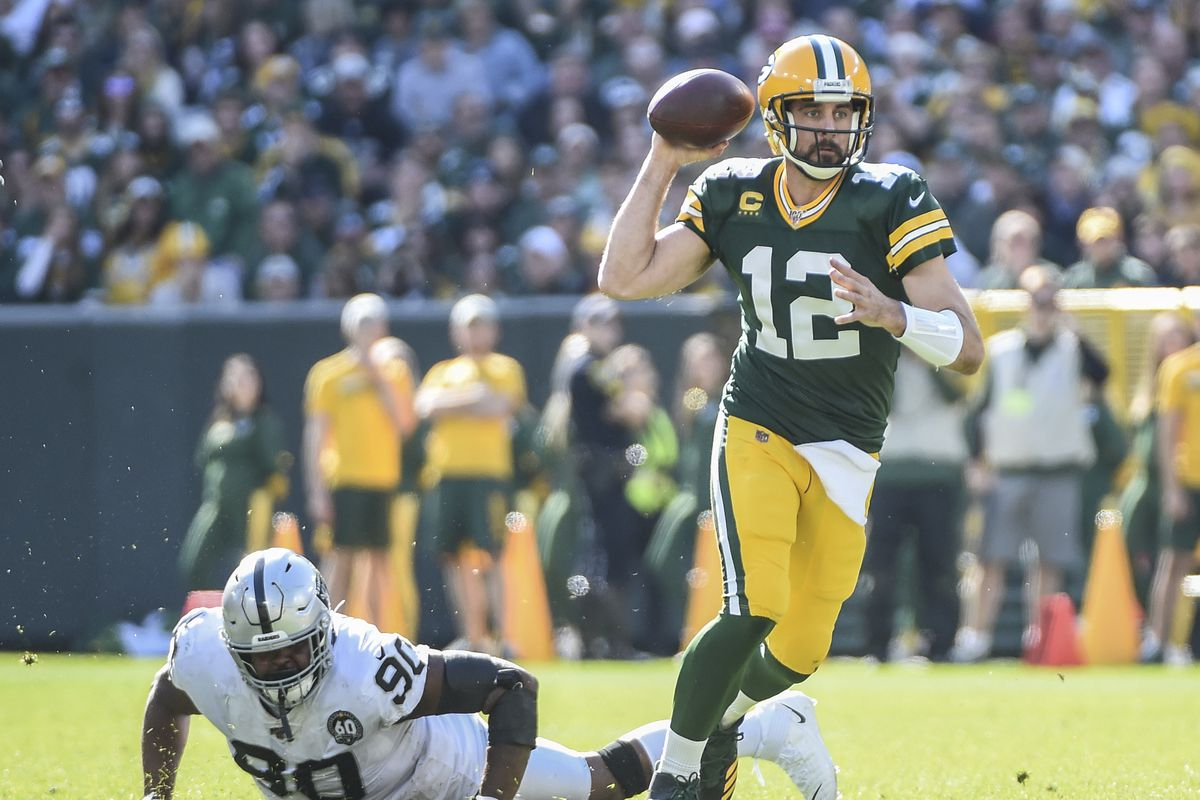 Green Bay Packers quarterback Aaron Rodgers throws a pass while under pressure from Oakland Raiders defensive tackle Johnathan Hankins in the second quarter at Lambeau Field.