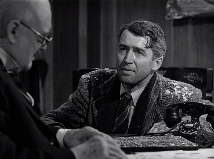 george bailey sits covered in snow at his lawayer's office
