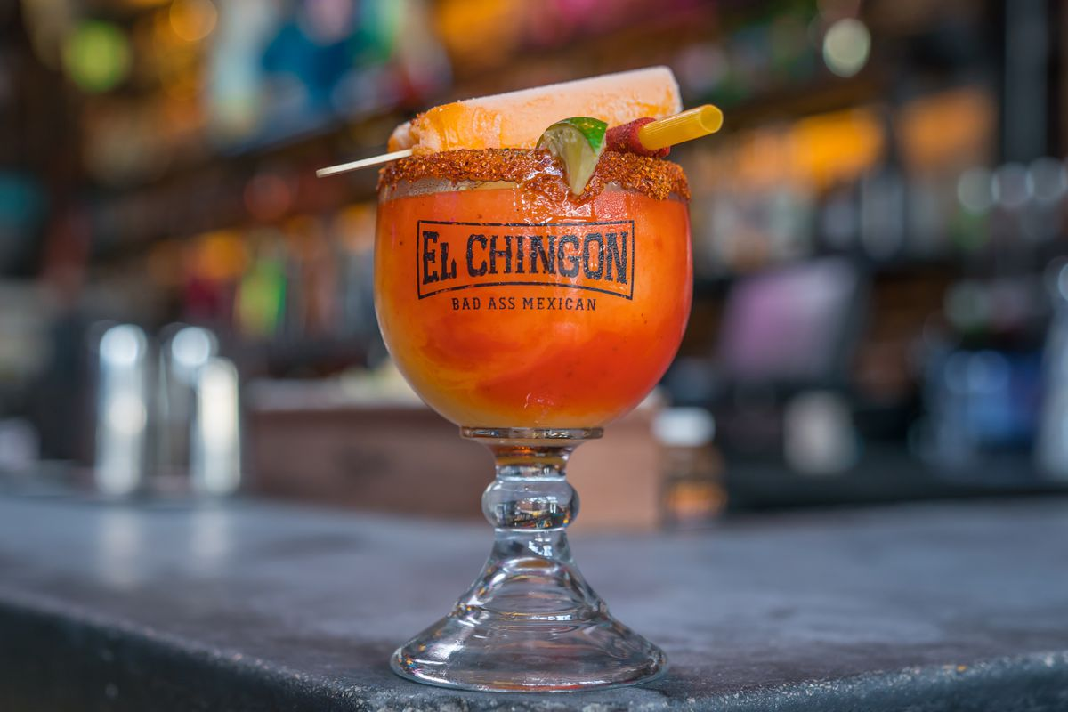 An orange cocktail in a goblet with a tajin rim and mexican candy garnish