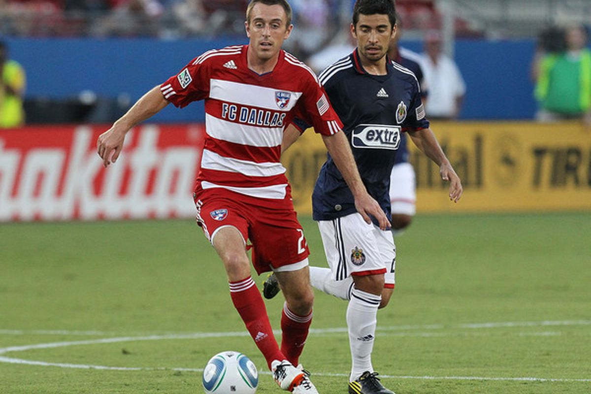 FRISCO TX - AUGUST 21:  Midfielder Eric Alexander #24 of FC Dallas dribbles the ball past Paulo Nagamura #26 of Chivas USA at Pizza Hut Park on August 21 2010 in Frisco Texas.  (Photo by Ronald Martinez/Getty Images)