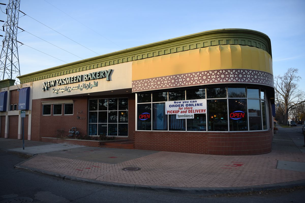 The exterior of New Yasmeen Bakery has a sign suggesting people order pickup or delivery.