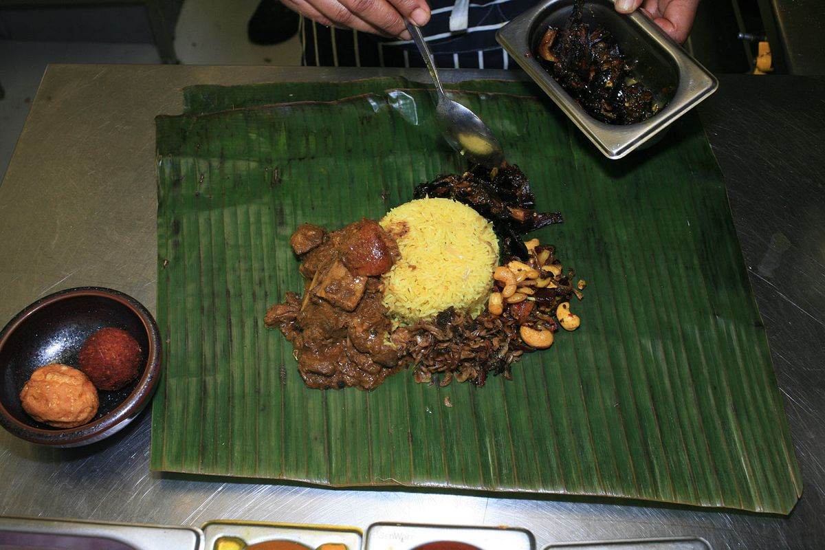 A chef adds brinjal moju, Sri Lankan caramelised aubergine, to lamprais