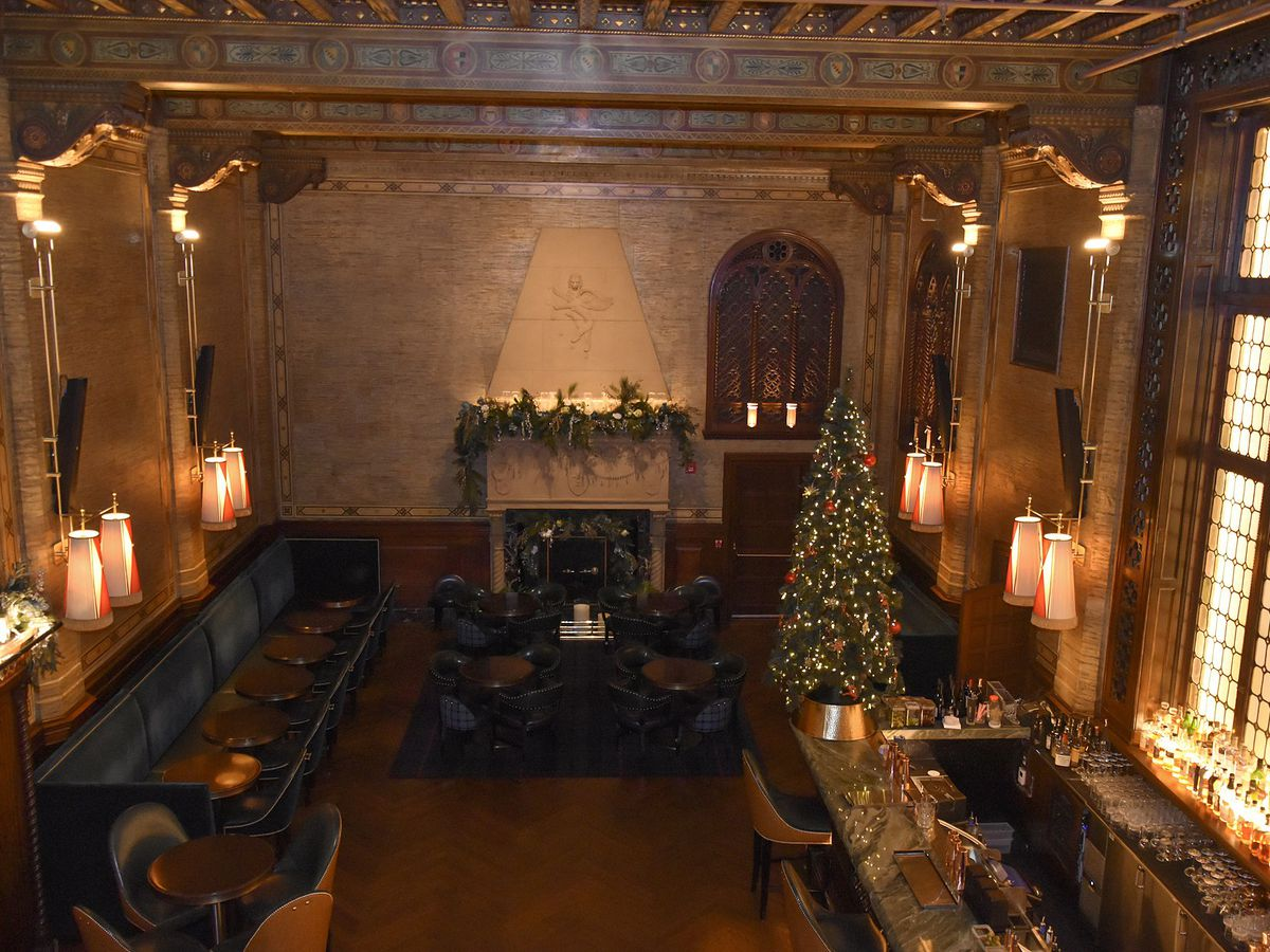 The interior of the Campbell Apartment in Grand Central Terminal in New York City. The room has high ceilings with an inlaid design, floor to ceiling windows, a fireplace, bar, tables, chairs, and booths.