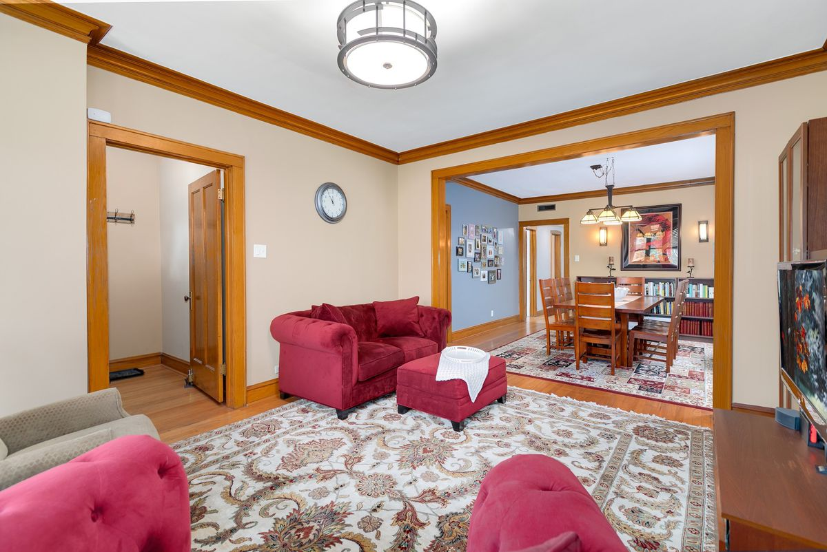 A view of a living room and attached dining room. There's wood trim on the walls and opening between rooms.