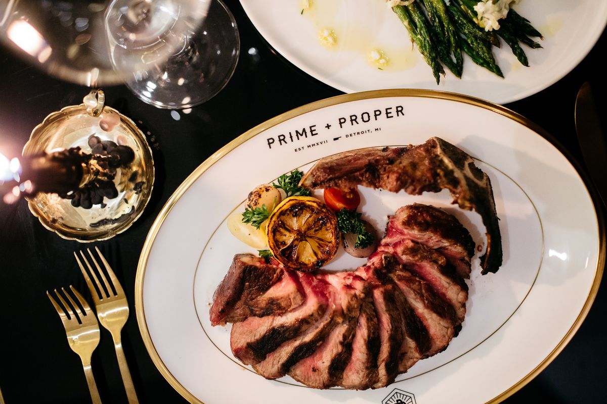 thinly sliced steak fanned out on a white plate with gold trim with prime and proper printed on it. The steak is garnished with a grilled lemon and surrounded by plates of asparagus and gold forks.