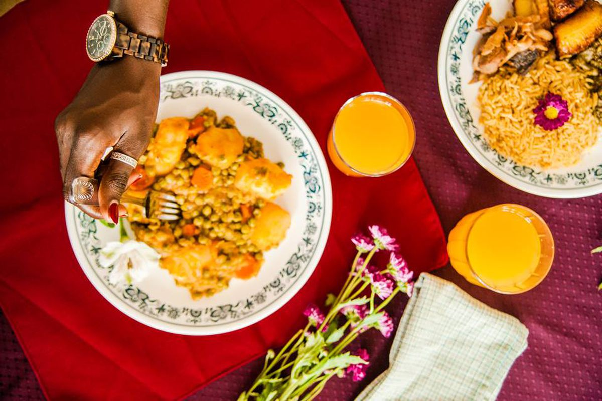 A hand with a fork digging into a yellow-colored stew of potatoes and peas over a red table cloth with yellow juice in plastic cups.