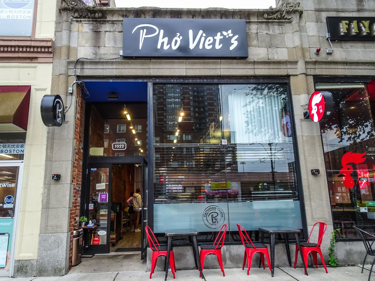 Exterior of a restaurant called Pho Viet's in a one-story gray stone building. Two small black tables, each with two bright red chairs, sit in front on the sidewalk.
