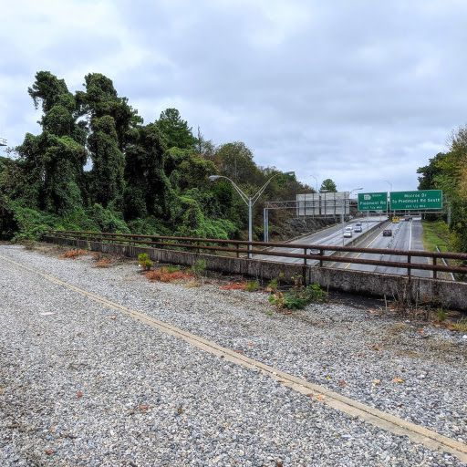 An old bridge with kudzu covered trees at left and a highway below.