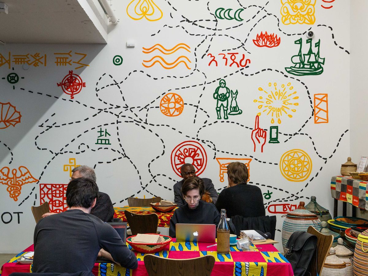 """Teranga diners sit at tables decorated with pink and yellow tablecloths, eating and working on their computers, as artist Ezra Wube's """"Project Junction"""" installation decorates the wall"""