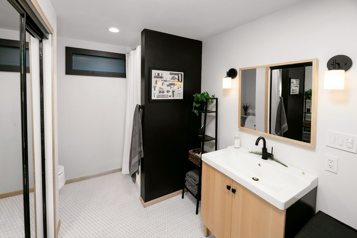 A bathroom with a white sink with natural wood cabinet underneath.