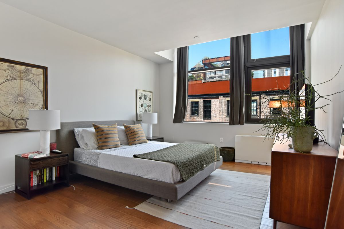A bedroom with a large bed, large windows, a skylight, and hardwood floors.